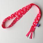 Roze keycord met lichtroze hartjes, afgewerkt met sierlintjes