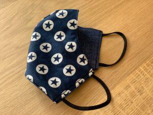 gevouwen mondkapje, één kant navy blauw met sterren en de andere kant jeans blauw