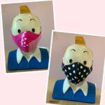 Roze vlak met linksboven een hoofd met roze mondkapje op met stippen en ruitenpatroon, rechtsonder een hoofd met zwart mondkapje op met witte stippen