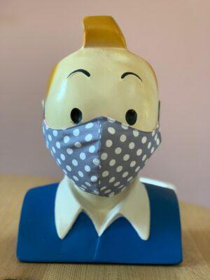 hoofd met grijs mondkapje op met witte stippen